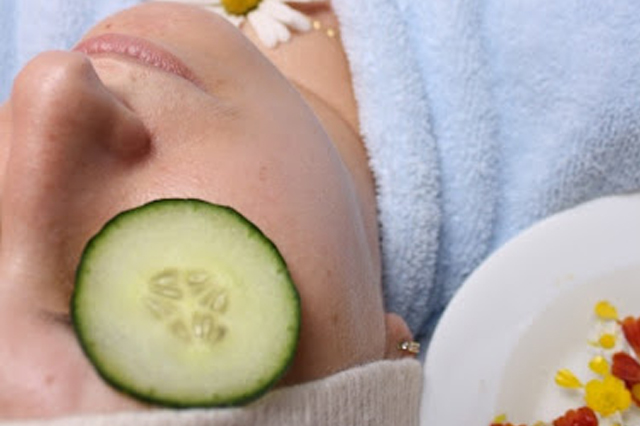 A woman getting facial with cucumbers on her eyes