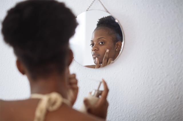 A woman applying facial cream