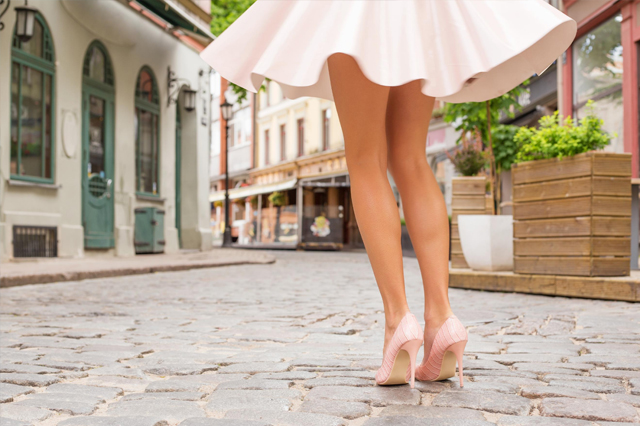 A woman with hairless legs twirling in a dress
