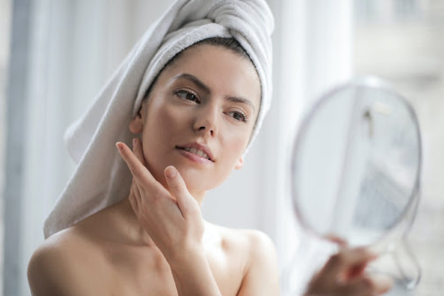A woman wearing a towel on her head while looking in a mirror