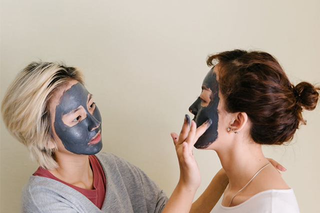 Two women applying charcoal masks on each others' faces.