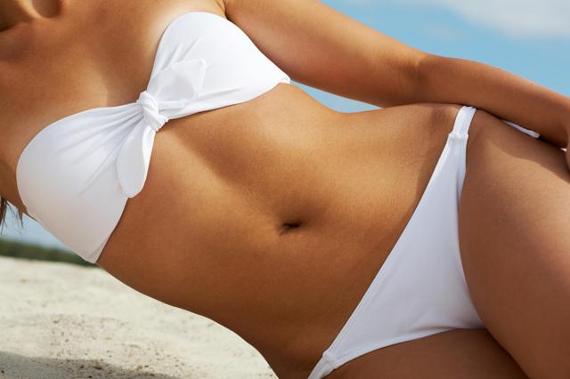 A woman wearing a bikini on the beach