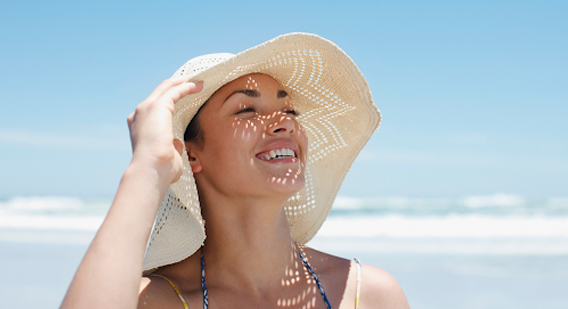 A woman smiling while wearing a hat for sun damage protection
