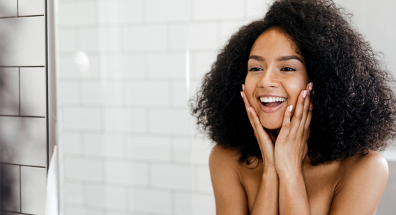 A woman admiring her skin in a mirror after a chemical peel