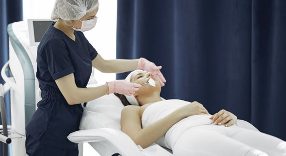 A skin specialist giving a facial to a client
