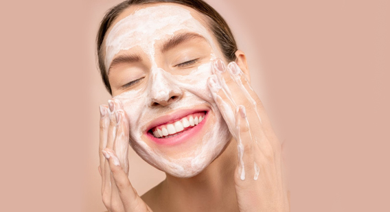 A woman smiling while applying a skincare product on her face